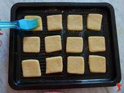 spennellare sulla superficie dei biscotti un tuorlo di uovo
